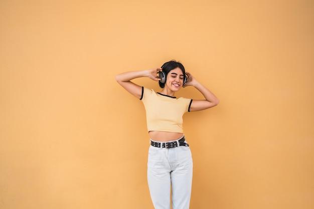 Ritratto di giovane donna latina che ascolta la musica con le cuffie contro lo spazio giallo. concetto urbano. Foto Gratuite