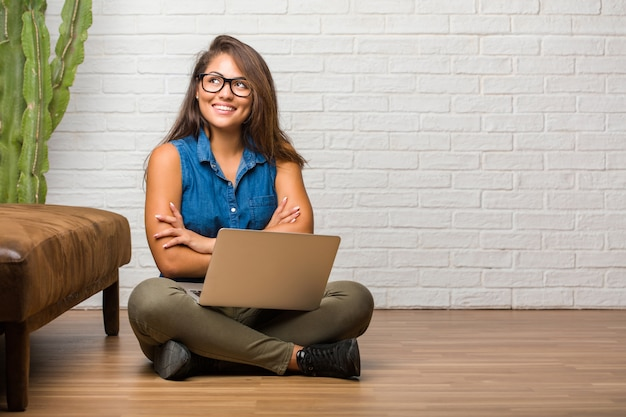 Portrait of young latin woman sitting on the floor looking up, thinking of something fun and having an idea, concept of imagination, happy and excited. holding a laptop. Premium Photo
