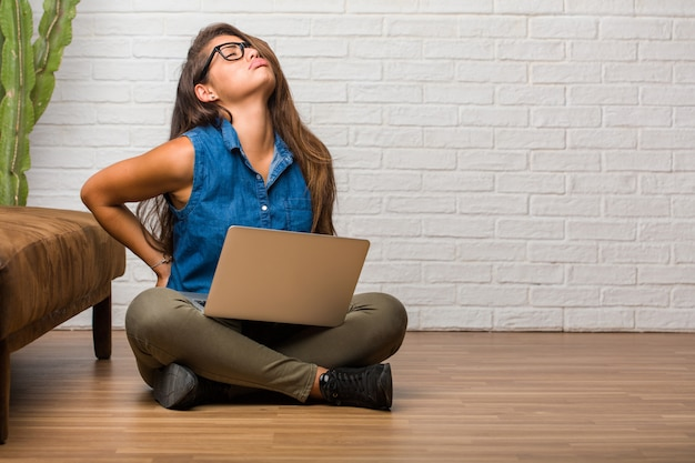 Portrait of young latin woman sitting on the floor with back pain due to work stress Premium Photo