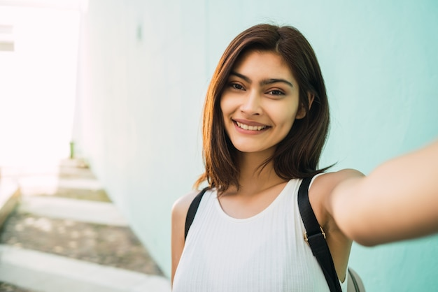 Portrait of young latin woman taking a selfie outdoors in the street. lifestyle and urban concept. Premium Photo