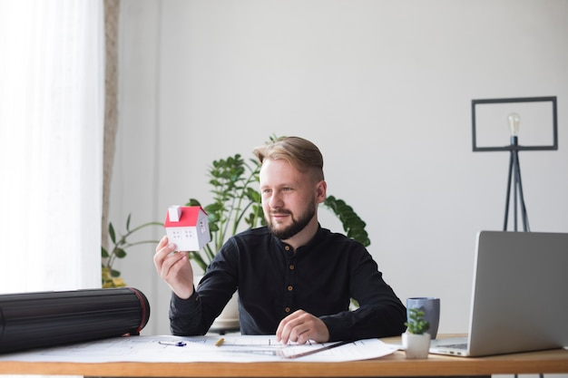 Portrait of a young male architecture holding house model while sitting in office Free Photo