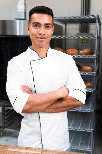 Portrait of a young male baker with his arms crossed looking at camera Free Photo