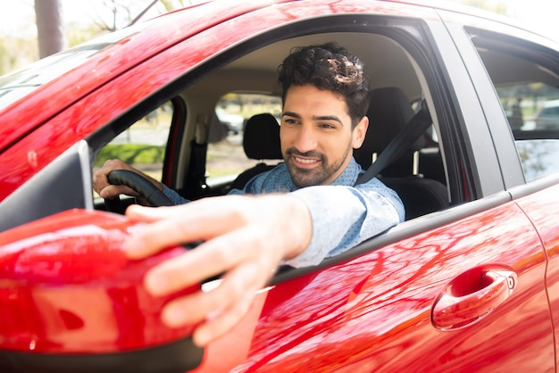 Portrait of young male driving his car and moving rear view wing mirror. Premium Photo