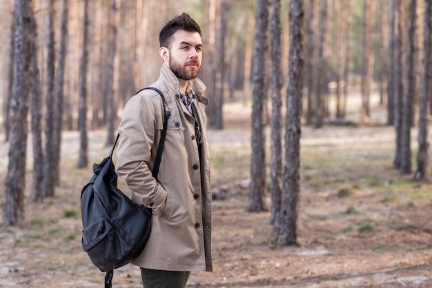 Portrait of a young male traveler holding backpack on his shoulder in the forest Free Photo