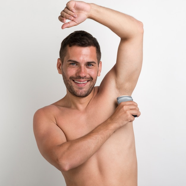 Portrait of young man applying roll on deodorant looking at camera Free Photo