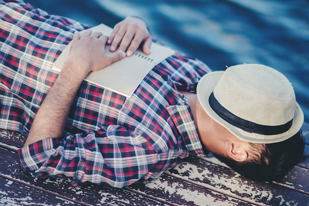 Portrait of young man book cover drowsiness causes sleep. Free Photo
