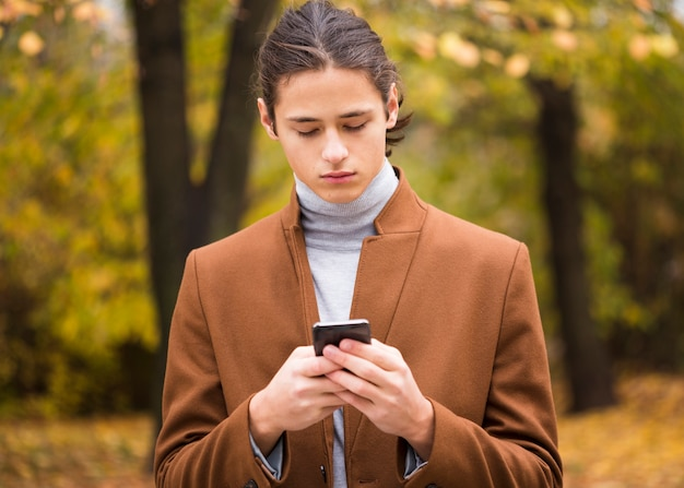 Portrait of young man checking his phone Free Photo