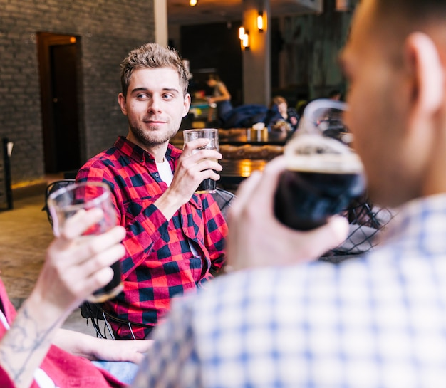 Portrait of a young man holding beer glass sitting with his friend Free Photo