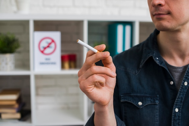 Portrait of young man holding cigarette Free Photo