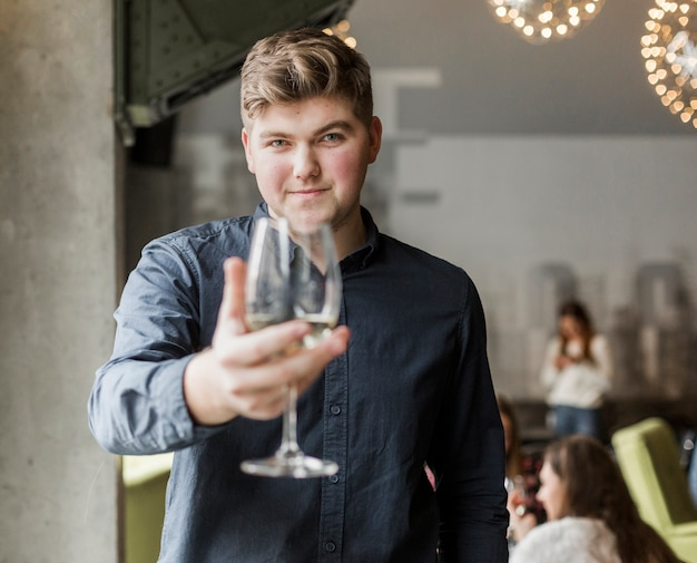 Portrait of young man holding a glass of wine Free Photo