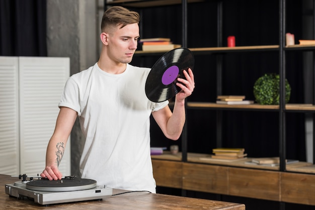 Portrait of a young man looking at vinyl record using retro vinyl player at home Free Photo