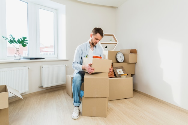 Portrait of a young man packing the cardboard boxes at home Free Photo