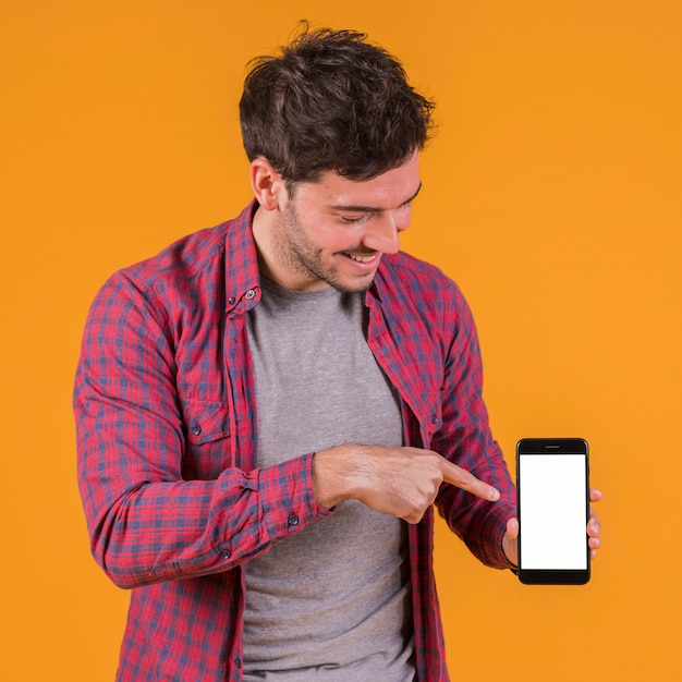 Portrait of a young man pointing his finger on mobile phone against an orange backdrop Free Photo