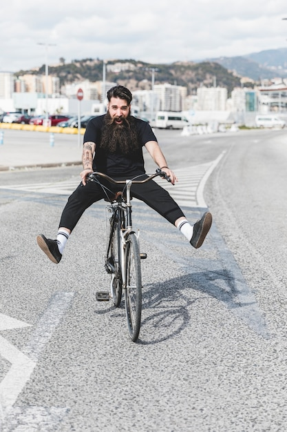 Portrait of young man riding bicycle on road with legs kicked out Free Photo
