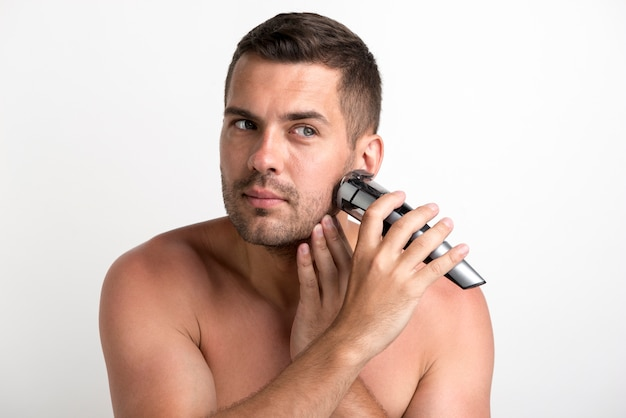 Portrait of young man shaving with trimmer against white background Free Photo