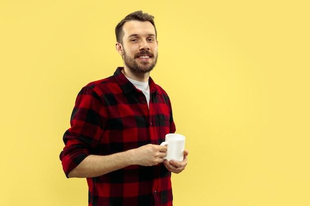 Ritratto di giovane uomo in camicia.vista frontale. colori alla moda. in piedi con una tazza. Foto Gratuite