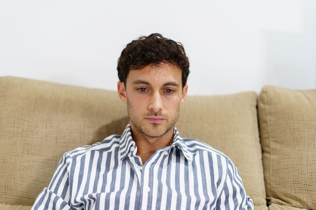 Portrait of a young man in a shirt with a concentrated expression on a sofa Premium Photo
