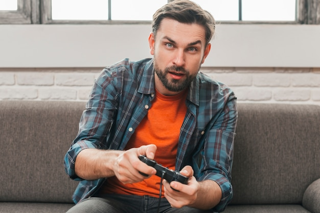 Portrait of a young man sitting on sofa playing the video game Free Photo