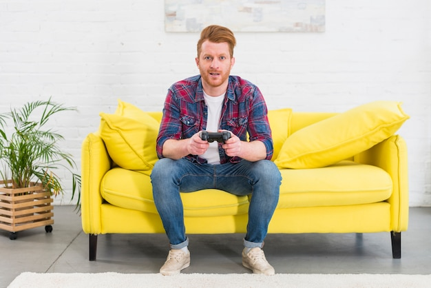 Portrait of a young man sitting on yellow sofa in the living room playing the video game Free Photo