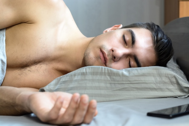 Portrait of a young man sleeping in bed on an orthopedic pillow is a special shape for a healthy spine, Premium Photo