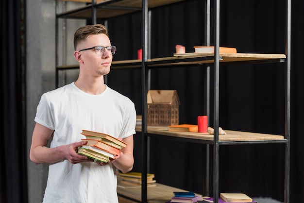 Portrait of a young man standing near the showcase holding colorful books in hand Free Photo
