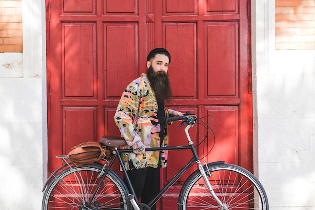 Portrait of a young man standing with bicycle in front of red door Free Photo