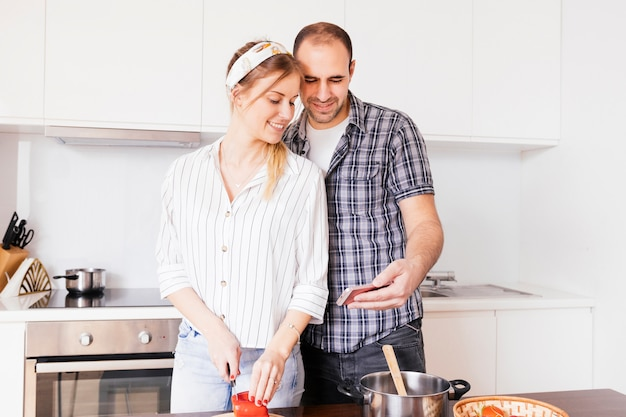 Portrait of a young man taking selfie on mobile phone with her wife cutting vegetable with knife Free Photo