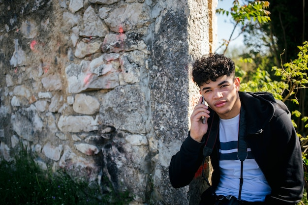 Portrait of young man talking on cellphone near stone wall Free Photo