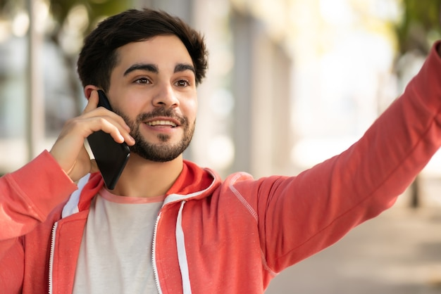 Ritratto di giovane uomo che parla al telefono e alzando la mano per fermare un taxi stando in piedi all'aperto sulla strada. concetto urbano. Foto Gratuite