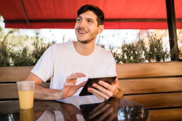Ritratto di giovane uomo utilizzando una tavoletta digitale mentre è seduto in una caffetteria. concetto di tecnologia e stile di vita. Foto Gratuite
