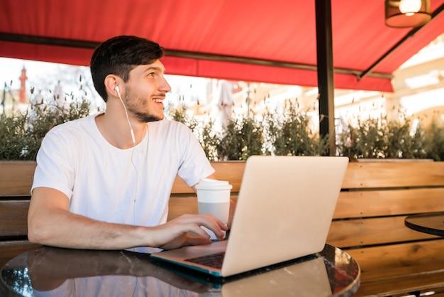 Ritratto di giovane uomo utilizzando il suo computer portatile mentre è seduto in una caffetteria. concetto di tecnologia e stile di vita. Foto Gratuite