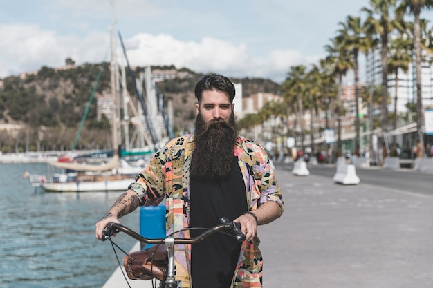 Portrait of a young man walking with bicycle near the coast Free Photo