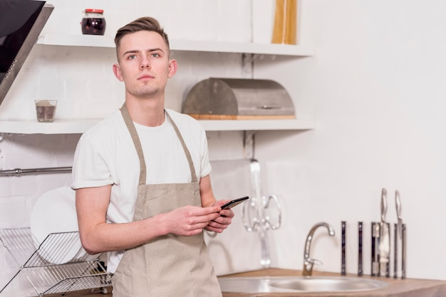 Portrait of a young man wearing apron holding mobile phone in hand looking away Free Photo