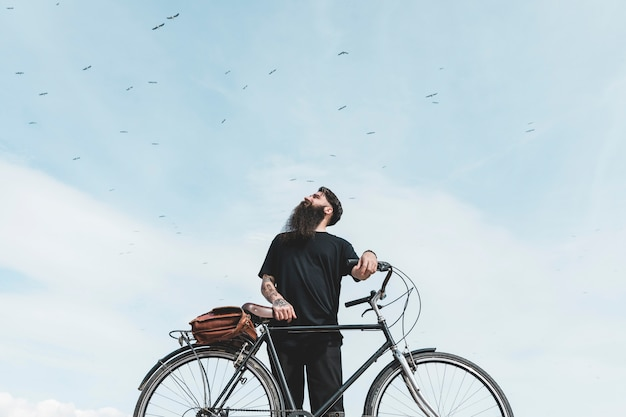 Portrait of a young man with bag on his bicycle looking at birds flying in the sky Free Photo