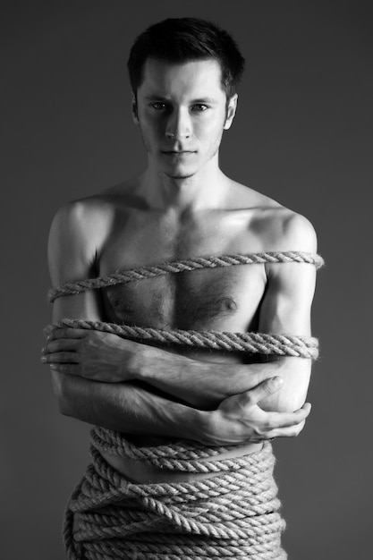 Portrait of young man with body tied up with ropes