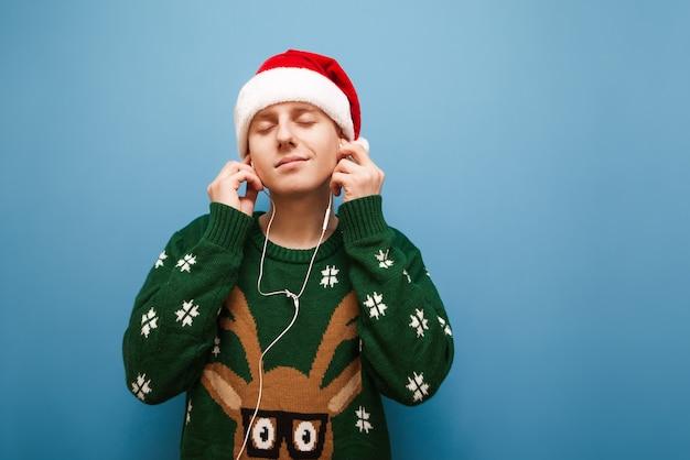 音楽を聴くクリスマスの肖像画の若い男 Premium写真