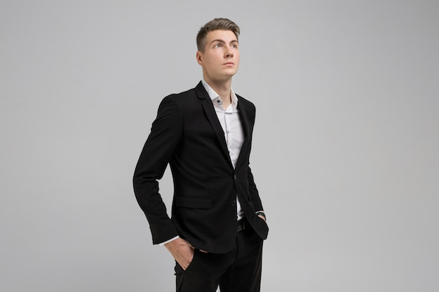 Portrait of young man with hands in pockets in black suit isolated on white background Premium Photo