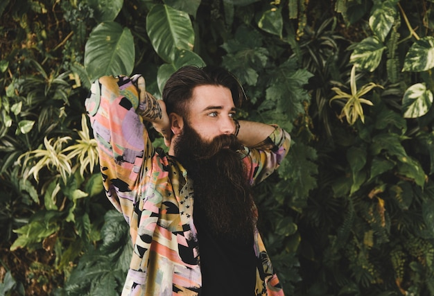 Portrait of a young man with long beard standing against green plants Free Photo