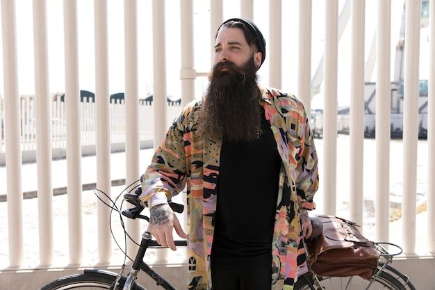 Portrait of a young man with long beard standing with bicycle in front of fence Free Photo