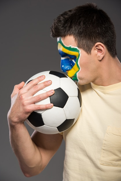 Portrait of young man with soccer ball and brazilian flag. Premium Photo