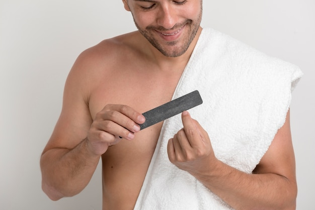Portrait of young man with white towel polishing his nails with fine Free Photo