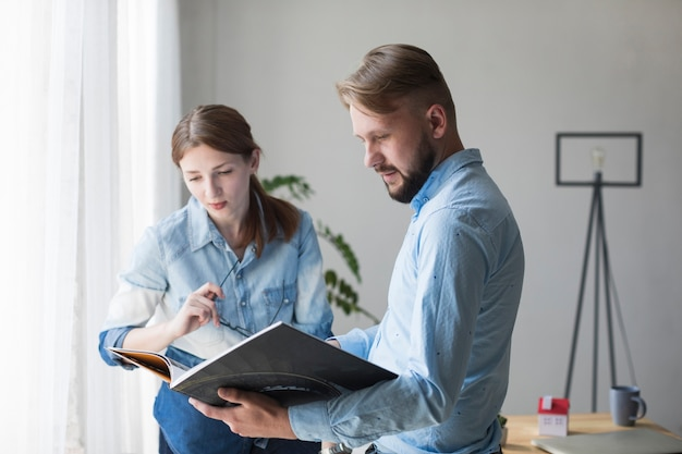 Portrait of young man and woman looking interior catalog at office Free Photo