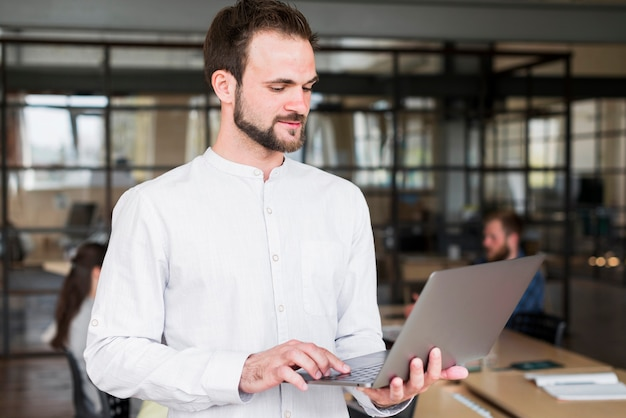 Portrait of a young man working on laptop at workplace Free Photo