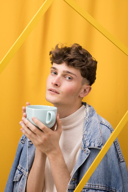Portrait of young man  in a yellow scene behind a frame Free Photo