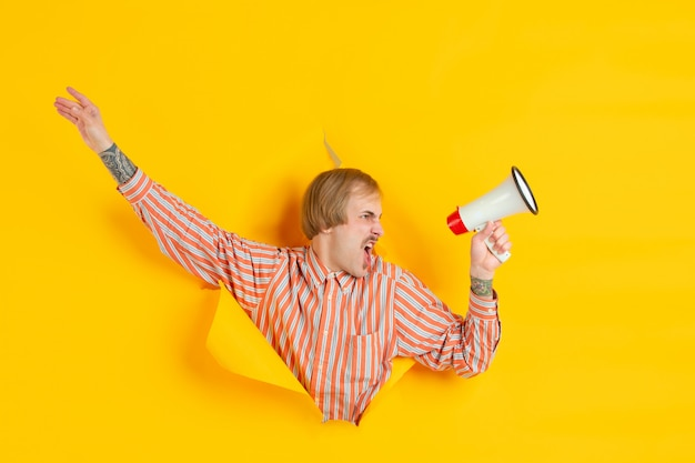 Portrait of young man on yellow torn breakthrought background Free Photo