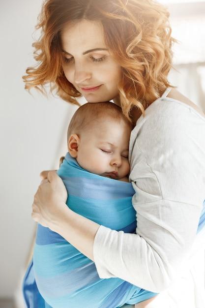Ritratto di giovane madre e figlio neonato che dorme sul petto della madre in fionda bambino blu. vibrazioni di felicità familiare. concetto di famiglia. Foto Gratuite