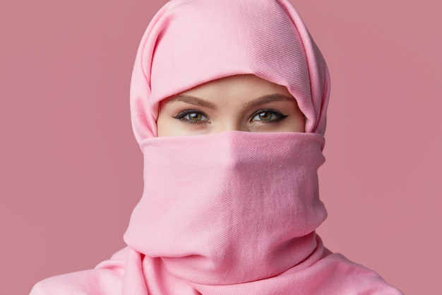 Portrait of young muslim arabian woman wearing colorful hijab. points finger to side. Premium Photo