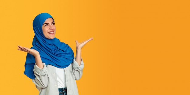 Portrait of young muslim woman isolated on yellow studio background Free Photo