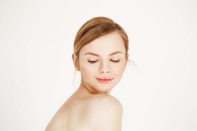 Portrait of young naked beautiful girl with healthy clean skin smiling looking down . facial treatment. Free Photo