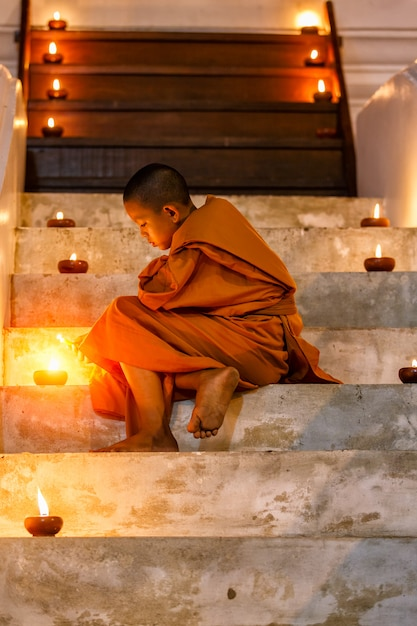 Portrait young novice monk sitting in the staircase at old temple Premium Photo